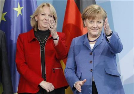 German Chancellor Angela Merkel (R) gestures while standing next to state premier of Germany's federal state of North Rhine-Westphalia Hannelore Kraft as she introduces a new two Euro coin in Berlin, January 26, 2011. REUTERS/Tobias Schwarz