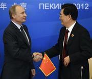 Лидеры России и Китая Владимир Путин и Ху Цзиньтао пожимают друг другу руки на саммите Шанхайской организации сотрудничества в Пекине 7 июня 2012 года. Фотография использована для иллюстрации к комментарию колумниста Рейтер Кристии Фрилэнд. REUTERS/Mark Ralston
