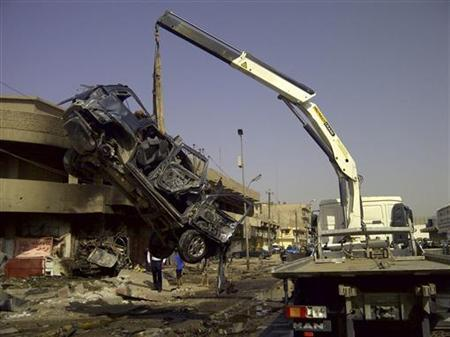 A burnt vehicle is removed from the site of a bomb attack, which killed Shi'ite pilgrims who were making their way to a religious festival, in Baghdad June 13, 2012. REUTERS/Saad Shalash