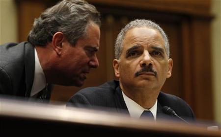 U.S. Attorney General Eric Holder receives information from counsel as he testifies before a House Oversight and Government Reform Hearing on ''Fast & Furious: Management Failures at the Department of Justice'' on Capitol Hill in Washington February 2, 2012. REUTERS/Kevin Lamarque