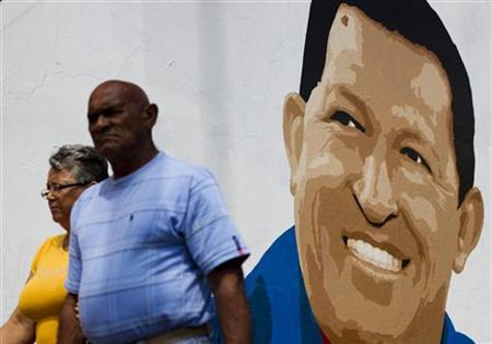 People walk past a mural of Venezuela's President Hugo Chavez in Caracas June 29, 2012. REUTERS/Carlos Garcia Rawlins