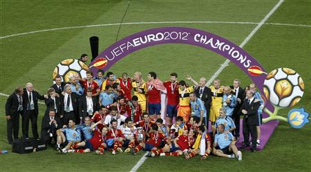 Spain's team players celebrate with the trophy after defeating Italy to win the Euro 2012 final soccer match at the Olympic Stadium in Kiev, July 1, 2012. REUTERS/Charles Platiau