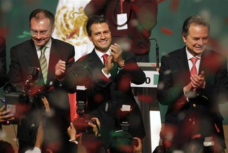 Enrique Pena Nieto (C), presidential candidate of the Institutional Revolutionary Party (PRI), stands next to campaign manager Luis Videgaray (L) and President of the PRI party Joaquin Coldwell as he greets supporters after exit polls showed him in first place, in Mexico City July 1, 2012. REUTERS/Tomas Bravo