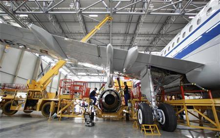 Employees install an engine for an A320 plane under construction at the final assembly line of Airbus factory in Tianjin municipality, June 13, 2012. REUTERS/Jason Lee