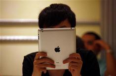 Мужчина смотрит на экран iPad в кафе в Пекине, 6 июня 2012 года. Apple Inc выплатила $60 миллионов китайской компании Proview Technology ради завершения продолжительного судебного спора о праве на марку iPad в Китае. REUTERS/David Gray