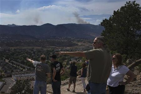 Residents point towards the Waldo Canyon Fire from a lookout point in Colorado Springs, Colorado June 30, 2012. REUTERS/Adrees Latif
