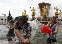 Люди купаются в фонтане на ВВЦ жарким днем в Москве 2 июля 2011 года. Москвичей ждет жаркая и солнечная рабочая неделя, прогнозируют синоптики. REUTERS/Sergei Karpukhin