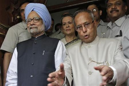 Former Finance Minister Pranab Mukherjee gestures to photographers as Chief of ruling Congress party Sonia Gandhi (C) and Prime Minister Manmohan Singh (in blue turban) watch at the parliament in New Delhi June 28, 2012. REUTERS/B Mathur