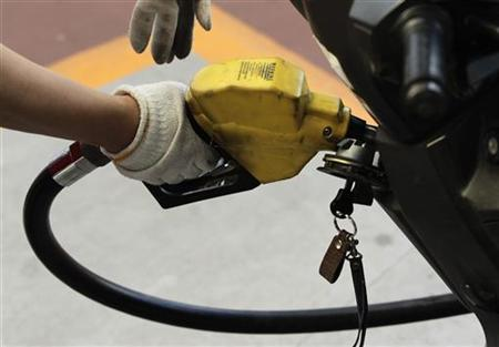 An employee fuels a motorcycle at a SK Energy gas station in central Seoul June 26, 2012. REUTERS/Woohae Cho