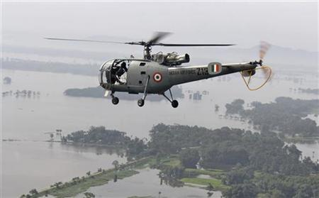 An Indian Air Force (IAF) helicopter, carrying relief supplies, flies over the flooded areas of the Sonitpur district in Assam July 1, 2012. REUTERS/Stringer