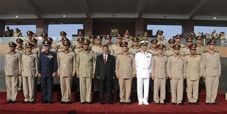 Egypt's new President Mohamed Mursi (C) and Field Marshal Mohamed Tantawi (5th L), head of Egypt's ruling Supreme Council of the Armed Forces (SCAF), pose for a picture during a ceremony where the military handed over power to Mursi at a military base in Hikstep, east of Cairo, June 30, 2012. REUTERS/Mohamed Abd El Moaty/Egyptian Presidency/Handout