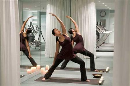 A woman practices yoga in the gym at Kimpton's Lorien Hotel and Spa in Washington, D.C. in this May 2009 handout. REUTERS/Fred Licht, Kimpton Hotels and Restaurants/Handout
