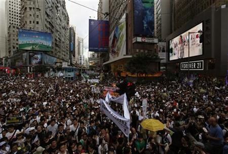 Thousands of protesters urging new leader Leung Chun-ying to step down crowd a street in Hong Kong's shopping Causeway Bay district July 1, 2012, during the 15th anniversary of the territory's handover to China. REUTERS/Bobby Yip
