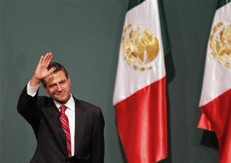 Enrique Pena Nieto, presidential candidate of the Institutional Revolutionary Party (PRI), waves after exit polls showed him in first place, in Mexico City July 1, 2012. REUTERS/Tomas Bravo