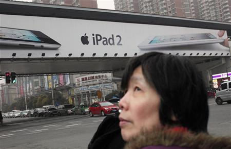 A woman stands near an Apple billboard advertising the iPad 2 in downtown Shanghai in this March 1, 2012 file photograph. REUTERS/Carlos Barria/Files