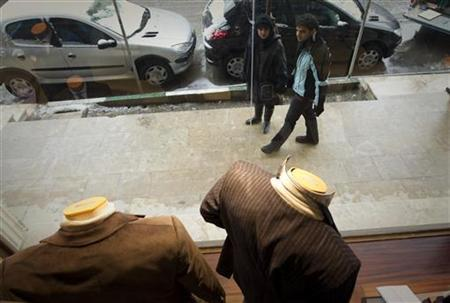 Pedestrians stop to look at imported suits at a high-street clothing store in north Tehran February 8, 2012. REUTERS/Caren Firouz