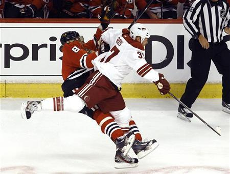 Chicago Blackhawks' Marian Hossa (L) is checked by Phoenix Coyotes' Raffi Torres during Game 3 of their NHL Western Conference quarter-final playoff hockey game in Chicago, Illinois April 17, 2012. Hossa was taken from the ice on stretcher following the play. REUTERS/Jim Young
