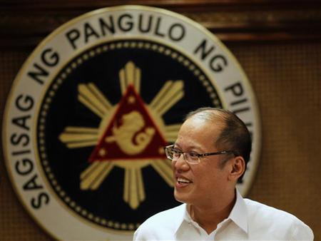 Philippine President Benigno Aquino smiles in front of a presidential seal during a government's oral immunization program for poor families at the presidential palace in Manila July 2, 2012. REUTERS/Erik De Castro