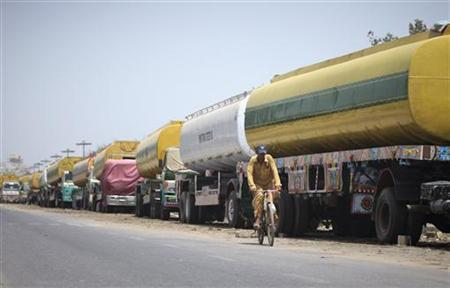 A man rides his bicycle past fuel tankers, which were used to carry fuel for NATO forces in Afghanistan, parked along a roadside in Karachi May 23, 2012. REUTERS/Akhtar Soomro/Files