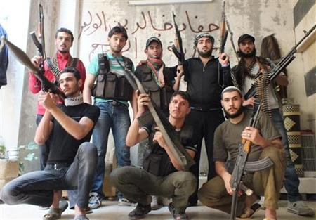 Members of rebel group Khaled ibin al Walid Fighters pose with their weapons at the frontline fighting against Syrian President Bashar al-Assad's forces at Hamidiyeh district in the central city of Homs July 1, 2012. REUTERS/Yazen Homsy