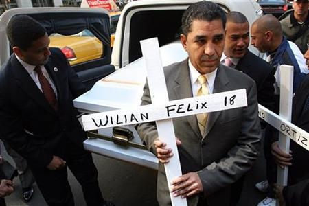 Adriano Espaillat holds a cross while other protesters unload a coffin from a hearse in front of Major League Baseball headquarters in New York on April 14, 2005. REUTERS/Seth Wenig