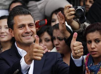 Enrique Pena Nieto, presidential candidate of the Institutional Revolutionary Party (PRI), shows his ink stained thumbs after casting his vote in Atlacomulco July 1, 2012. REUTERS/Tomas Bravo