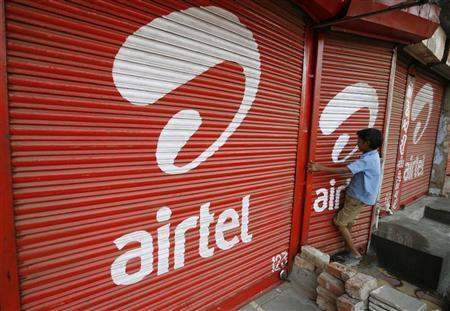 A boy closes the shutter of a shop painted with an advertisement for Bharti Airtel in the western Indian city of Ahmedabad May 5, 2011. REUTERS/Amit Dave