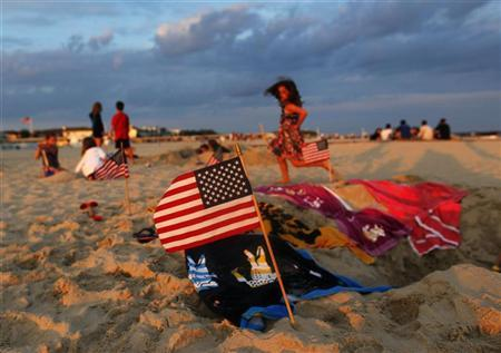 A U.S. flag is seen in the sand as children play during July 4th weekend celebrations in Atlantic Beach New York July 2, 2011. REUTERS/Shannon Stapleton