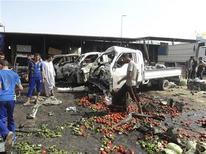 Местные жители изучают место взрыва бомбы в Кербале, 3 июля 2012 года. Взрыв автомобиля на оживленном рынке в городе Эд-Дивания на юге Ирака унес жизни по меньшей мере 25 человек, еще 40 получили ранения, сообщил представитель властей региона. REUTERS/Mushtaq Muhammed