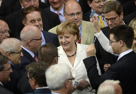 German Chancellor Angela Merkel (C) and other delegates cast their ballots during the vote for ratification of the European Union fiscal pact in the Reichstag, the seat of the German lower house of parliament the Bundestag, in Berlin June 29, 2012. REUTERS/Fabian Bimmer