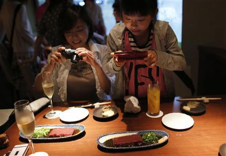 Yurika Miki (R) and her mother Yoshiko take photos of raw beef liver sashimi before eating them at a restaurant in Tokyo June 28, 2012. REUTERS/Toru Hanai