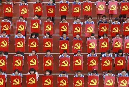 Middle school students hold cardboards featuring the emblems of the Communist Party of China as they pose for photographs during an event to celebrate the party's 91st anniversary, in Suining, Sichuan province June 30, 2012. REUTERS/China Daily
