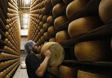 An employee stacks a wheel of cheese on the storage shelves at a diary plant in Litovel, one of the world's biggest producer of traditionally made parmesan cheese, June 27, 2012. REUTERS/Petr Josek