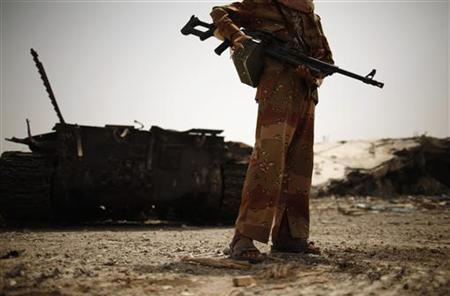 An army soldier stands near a tank and a building destroyed during recent fighting between the army and al Qaeda-linked militants in the southern Yemeni city of Zinjibar, Abyan June 21, 2012. REUTERS/Khaled Abdullah
