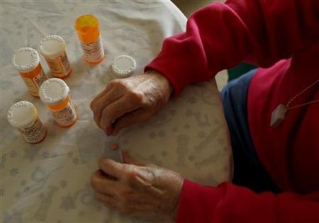 Inez Willis, a senior citizen, sorts her daily medical prescriptions at her independent living apartment in Silver Spring, Maryland April 11, 2012. REUTERS/Gary Cameron