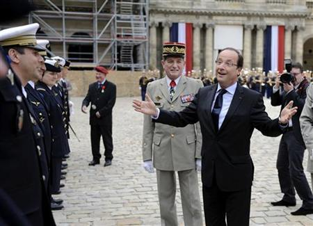 France's President Francois Hollande (R), flanked by his military chief of staff Benoit Puga (C), gestures during a military ceremony at the Hotel des Invalides in Paris July 3, 2012. REUTERS/Eric Feferberg/Pool