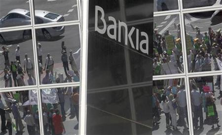 Minority shareholders protesting against the abuses of banks and saving banks are reflected on the headquarters of Spain's lender bank Bankia in Madrid June 23, 2012. REUTERS/Andrea Comas