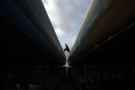 A man walks across the tops of fuel tankers, which were used to carry fuel for NATO forces in Afghanistan, parked at a compound in Karachi July 3, 2012. The United States and Pakistan are expected to agree soon on the reopening of land routes crucial to supplying NATO troops in Afghanistan, a Pakistani official said on Monday, a move that could ease a seven-month crisis in the two countries' ties. REUTERS/Athar Hussain