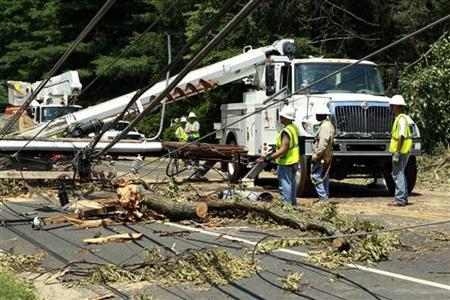 Utility workers try to free up power lines after a huge tree fell across major road in Falls Church, Virginia July 2, 2012. REUTERS/Kevin Lamarque