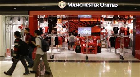 Shoppers walk past a Manchester United merchandise store at a mall in Singapore June 14, 2012. REUTERS/Tim Chong/Files