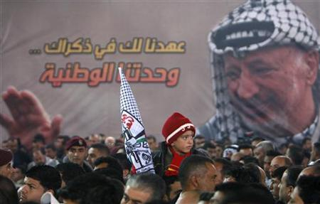 A Palestinian boy holds a Fatah flag during an event marking the 7th anniversary of the late Palestinian leader Yasser Arafat in the West Bank city of Ramallah in this November 16, 2011 file photo. REUTERS/Mohamad Torokman/Files