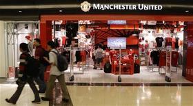 """Покупатели проходят мимо магазина с экипировкой клуба """"Манчестер Юнайтед"""" в Сингапуре, 14 июня 2012 года. Английский футбольный клуб """"Манчестер Юнайтед"""" выбрал Нью-Йоркскую фондовую биржу (NYSE) в качестве площадки для первичного размещения акций. REUTERS/Tim Chong"""