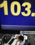 Трейдер следит за ходом торгов в Токио, 7 мая 2012 года. Азиатские фондовые рынки закрылись разнонаправлено под влиянием локальных факторов, хотя инвесторы сохраняют надежду на стимулирующие меры центробанков. REUTERS/Yuriko Nakao