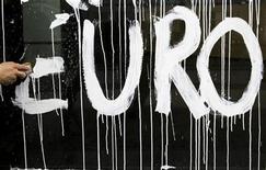 """Мойщик окон стирает надпись """"евро"""" с поверхности двери Академии искусств в Берлине, 3 июля 2012 года. Евро снижается к доллару и иене на фоне ожиданий снижения процентной ставки Европейского Центробанка в четверг. REUTERS/Thomas Peter"""