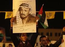 Палестинец держит постер с изображением покойного палестинского лидера Ясира Арафата на церемонии, посвященной седьмой годовщине его смерти, 13 ноября 2011 г. Руководство Палестины разрешило эксгумацию тела своего бывшего лидера Ясира Арафата после появившихся подозрений в том, что его смерть в 2004 году наступила в результате отравления радиоактивным элементом полоний-210.  REUTERS/Mussa Qawasma