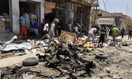 Residents gather at the site of a bomb attack in a market in the eastern Iraqi town of Zubaidiya in Kut, 100 km (60 miles) southeast of Baghdad, July 4, 2012. REUTERS/Jaafer Abed