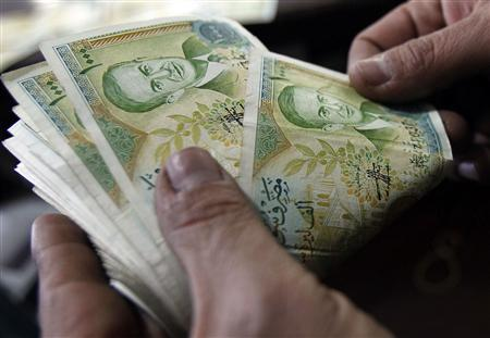 A cashier counts Syrian currency notes in Amman, in this December 6, 2011 file photo. For many low-wage earners, who make up the majority of Syria's 20 million population, cheaper prices at state supermarkets, reminiscent of those in the Soviet Union, offer some reprieve from the economic fallout of the uprising, which has hammered key hard currency revenues from oil and tourism and sent the Syrian pound plunging. REUTERS/Ali Jarekji/Files (