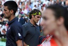 O sérvio Novak Djokovic (esquerda) caminha ao lado do suíço Roger Federer (centro) durante uma partida no estádio de Roland Garros em Paris. Federer e Djokovic vão se enfrentar na semifinal em Wimbledon. 8/06/2012 REUTERS/Nir Elias