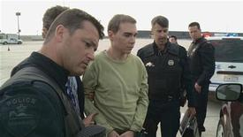 Luka Rocco Magnotta, 29, accused of killing a Chinese student, Jun Lin, and sending his feet and hands in the mail to the offices of two Canadian political parties and two Vancouver schools, is escorted off a plane from Germany by Montreal police in Montreal June 18, 2012 in this handout photo. Magnotta, who is accused of first-degree murder, was arrested in a cyber cafe in Berlin two weeks ago. REUTERS/SPVM/Handout