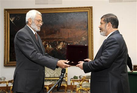 Egypt's first Islamist president Mohamed Mursi (R) honours Judge Hossam El Gheriany, chairman of the constituent assembly, at the presidential palace in Cairo July 3, 2012. REUTERS/Ahmed Morad /Egyptian Presidency/Handout